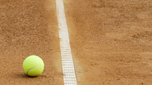 Woman lifting ball outside line of tennis court with racket, feet close up video