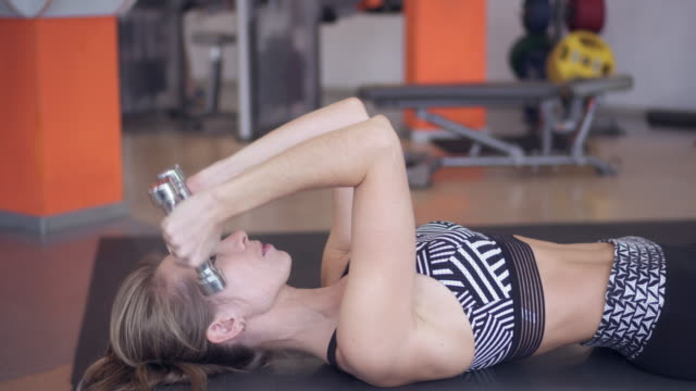 woman lifting dumbbells while doing workout - napinać mięśnie filmów i materiałów b-roll