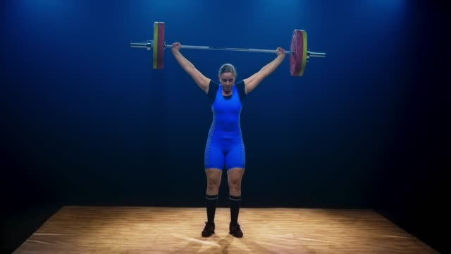 LD Woman lifting the barbell by performing the snatch lift at the weightlifting competition