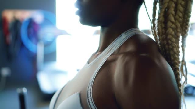 woman lifting weight plate while exercising in gym - napinać mięśnie filmów i materiałów b-roll