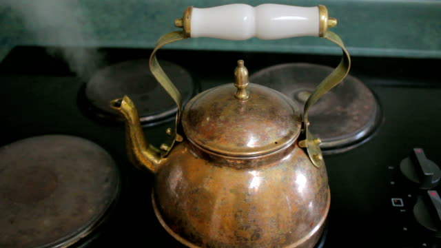 a woman lifts a copper tea kettle from a stove top - teiera video stock e b–roll