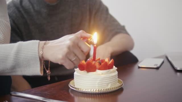 Woman lighting a candle on strawberry sponge cake on Christmas