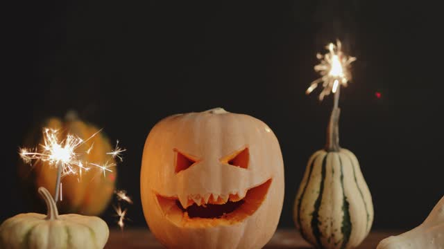 Woman lighting up a Halloween spooky pumpkins with sparklers candles Woman lighting up a Halloween spooky pumpkins with sparklers candles, scary face glowing in the darkness, 4k, cinematic, medium close-up, steady shot ghost icon stock videos & royalty-free footage