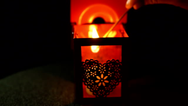 A woman lights a candle from a match in a red flashlight on a black background. video