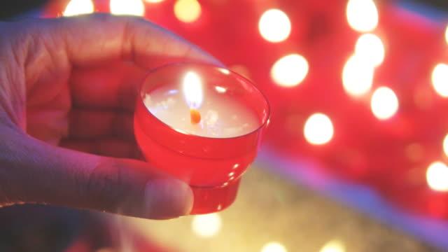 여자는 교회에서 제단 근처 촛불을 조명. - 촛불 조명 장비 스톡 비디오 및 b-롤 화면