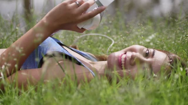 Woman listen to music on mobile phone, Looking at Camera