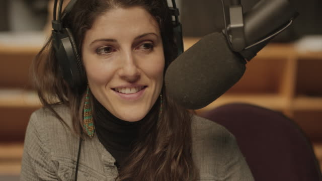 vidéos et rushes de une femme écoute et la parole dans un studio de radio - podcasting