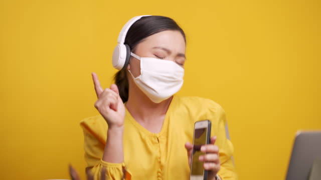 Woman listening music and dance over yellow background video
