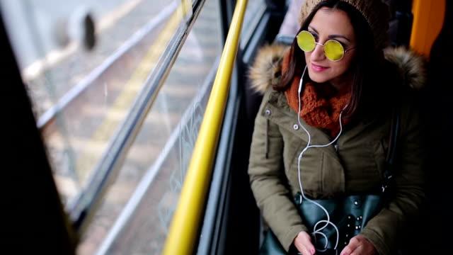Escuchar música de mujer en su teléfono inteligente en autobús de la carretilla - vídeo