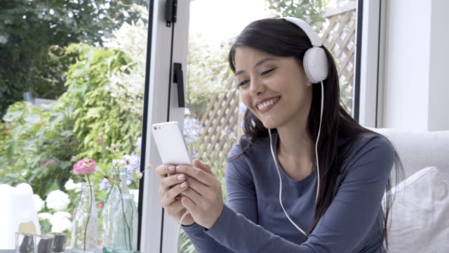 Woman listening music with headphones while using a smartphone