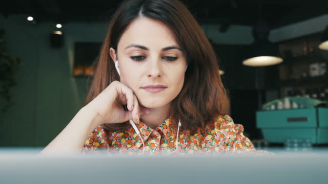 Woman listening podcast. Young woman at cafe listening podcast show using a laptop. She is very interested about the subject. headphones stock videos & royalty-free footage