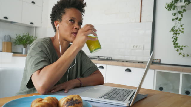 Mujer escuchas podcasts en la cocina portátil. - vídeo