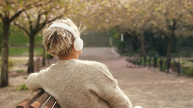 Woman listening to music in a park