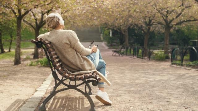 woman listening to music in a park - krótkie włosy filmów i materiałów b-roll