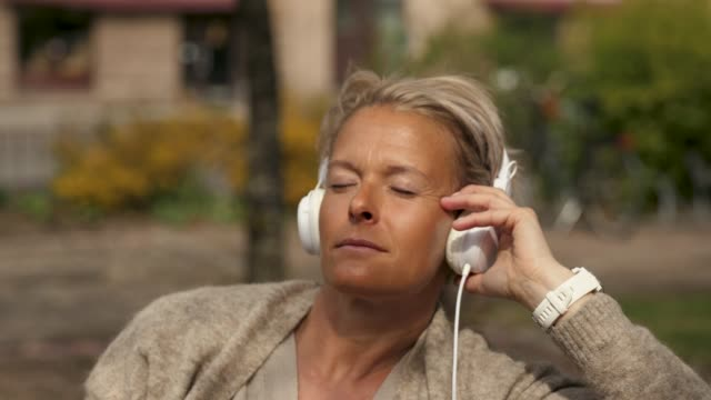 woman listening to music in a park - 50 54 lata filmów i materiałów b-roll