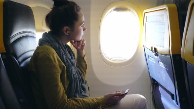 stockvideo's en b-roll-footage met vrouw luisteren naar muziek in vliegtuig - zakenreis