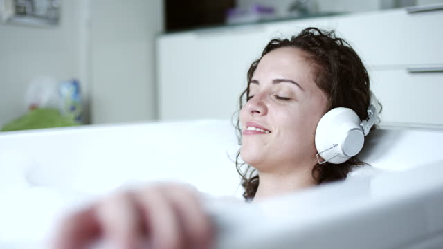 Woman listening to music in bathtub Young woman listening to music in bathtub at home indulgence stock videos & royalty-free footage