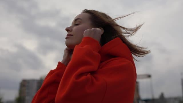 donna che ascolta musica nella fredda giornata autunnale, umore, nuvoloso - auricolari wireless video stock e b–roll