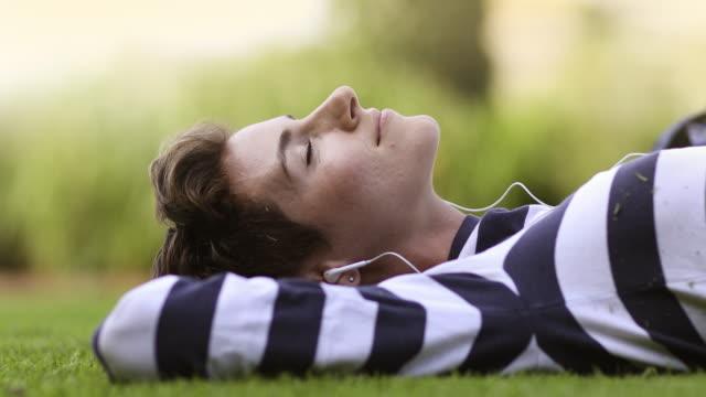 kvinna som lyssnar på musik i parken - summer sweden bildbanksvideor och videomaterial från bakom kulisserna
