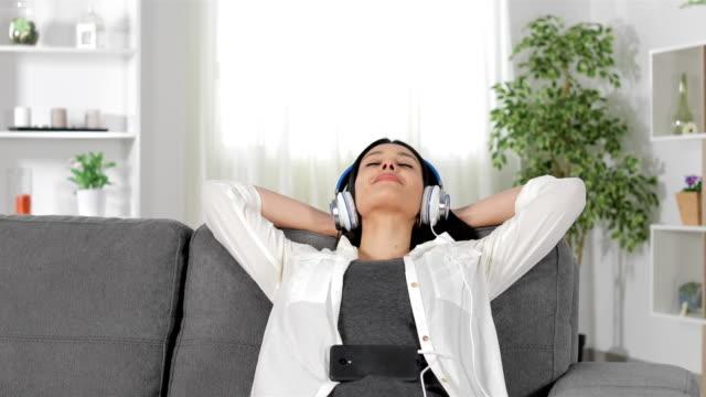 vídeos de stock, filmes e b-roll de mulher, ouvir música relaxante num sofá - relevo