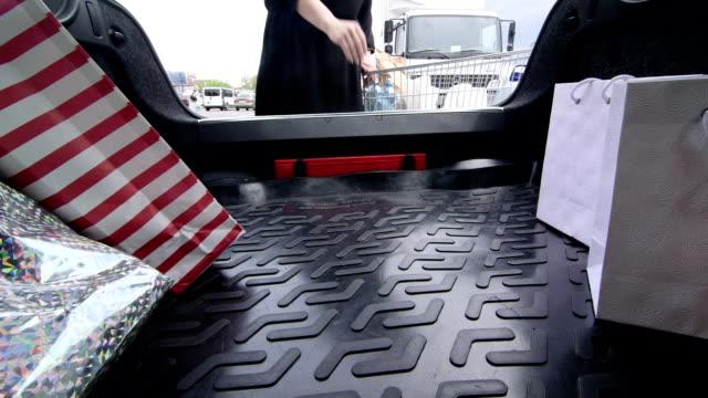 Femme de chargement de son Coffre de voiture avec épicerie - Vidéo