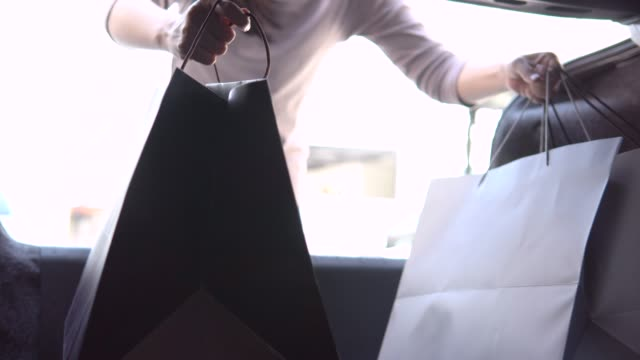 woman loading her car trunk with shopping bags - borsa della spesa video stock e b–roll