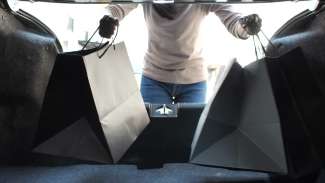 Femme chargeant son tronc de voiture avec des sacs de magasinage - Vidéo