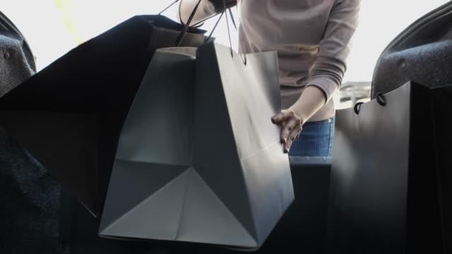 Femme son sac à provisions de chargement dans le coffre de voiture - Vidéo