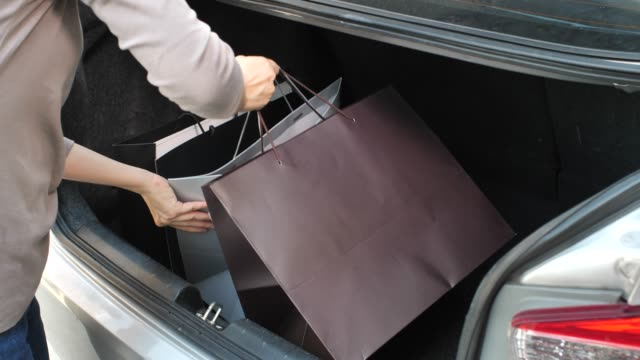 Woman loading her Shopping Bag into car trunk