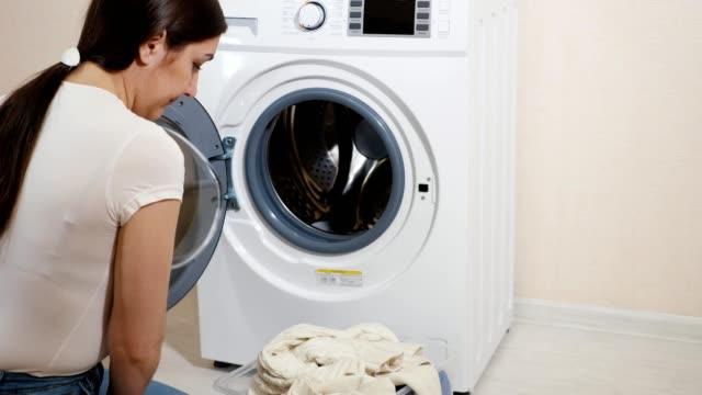 frau lädt kleidung in waschmaschine sitzend auf dem boden - waschmaschine wand stock-videos und b-roll-filmmaterial