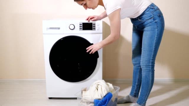 frau lädt schmutzige kleidung in waschmaschine in der nähe von beige wand - waschmaschine wand stock-videos und b-roll-filmmaterial