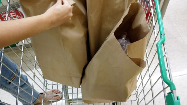 woman loads groceries in paper bags into shopping cart - portare video stock e b–roll