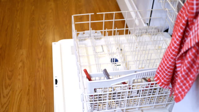 Woman loads up a dishwasher with dirty dishes in home kitchen Woman loads up a dishwasher with dirty dishes in home kitchen dishwasher stock videos & royalty-free footage