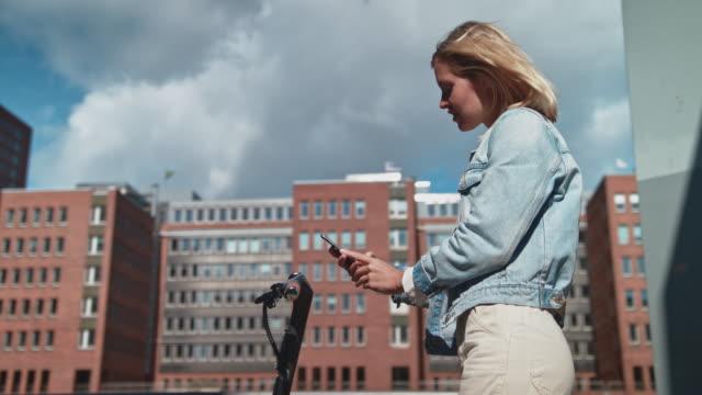 donna blocca scooter elettrico push con cellulare - monopattino elettrico video stock e b–roll