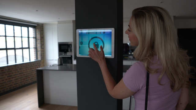 Woman locking her house with an intelligent home system using a tablet - technology concepts