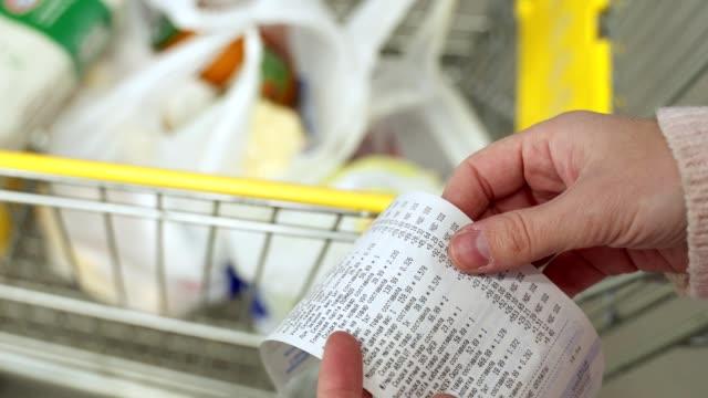 vídeos de stock, filmes e b-roll de mulher procurando um cheque de um supermercado. acompanhamento e orçamento de despesas - bico