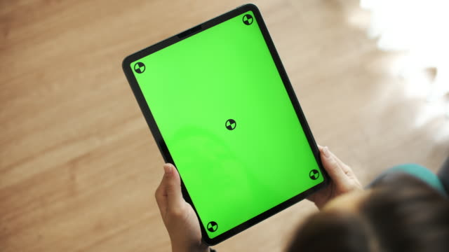 Woman Looking and Using Digital tablet with green screen