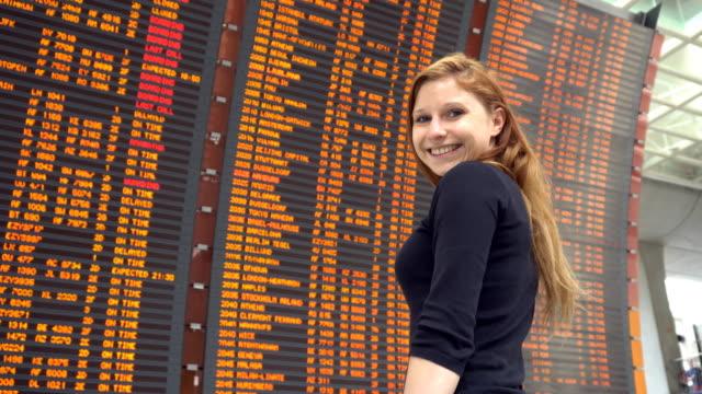 woman looking at airplane flight information board at airport - decollare attività video stock e b–roll