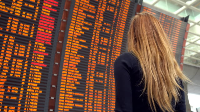 Woman looking at airport departure board
