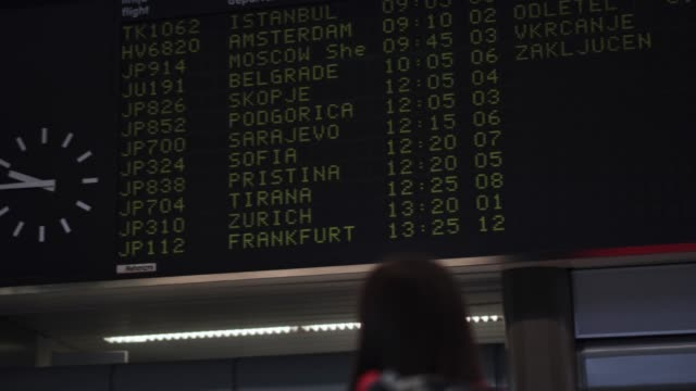 woman looking at airport departure board - табло вылетов и прилётов стоковые видео и кадры b-roll