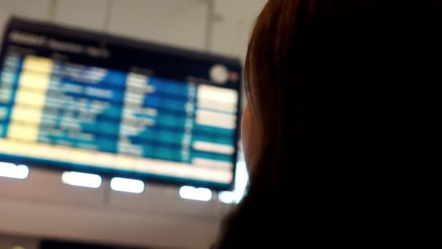 kvinna tittar på flyg platsen visa ombord, kontrol lera avgång flygning status närbild - billboard train station bildbanksvideor och videomaterial från bakom kulisserna