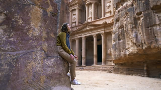 Woman looking at Al-Khazneh in Petra Young Caucasian woman  looking at Al-Khazneh in Petra ancient architecture stock videos & royalty-free footage