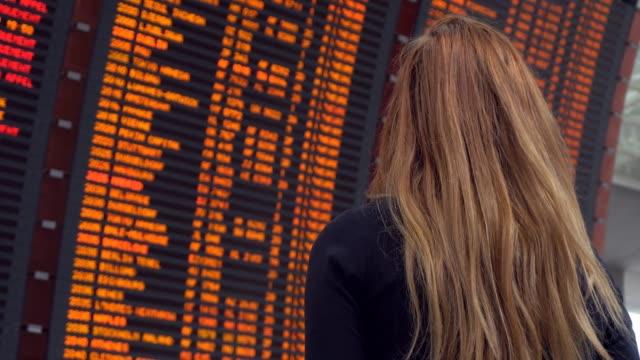 woman looking at arrival departure board - табло вылетов и прилётов стоковые видео и кадры b-roll