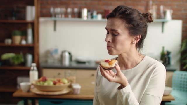 vídeos de stock e filmes b-roll de woman looking at camera with fancy cake in hand. girl biting dessert at home. - bolo sobremesa