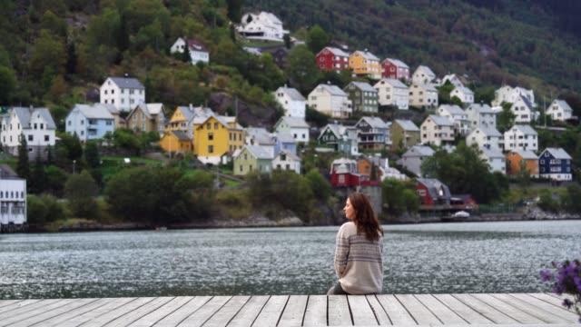 vídeos de stock e filmes b-roll de woman looking at cityscape  of odda town in norway - noruega