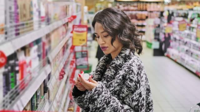 woman looking at cosmetics in supermarket. female buying body care products - brązowe włosy filmów i materiałów b-roll