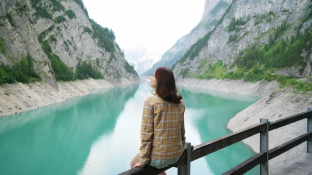 Woman looking at dam in Swiss Alps