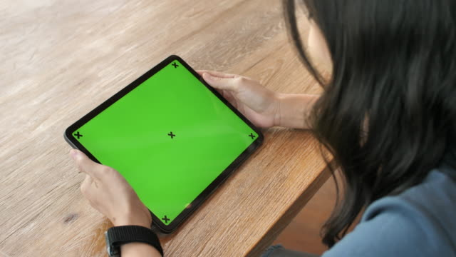 Woman Looking at Digital tablet with Green screen on wood desk