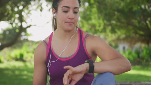 woman looking at her watch in a park - flessibilità video stock e b–roll