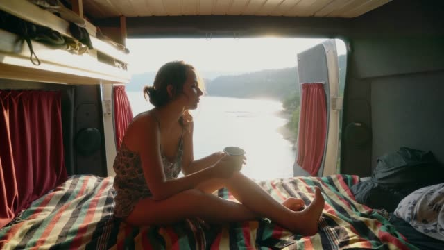 Woman looking at Lake of Sainte Croix and drinking tea in camper van Young Caucasian woman looking at Lake of Sainte Croix and  drinking tea in camper van rv interior stock videos & royalty-free footage